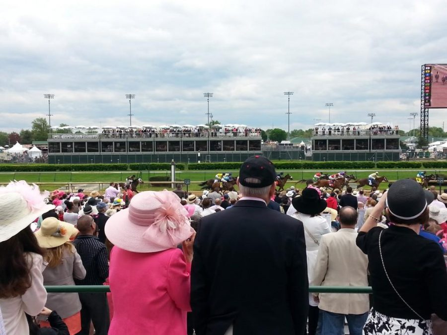 The morning of Kentucky Oaks Day as a race comes down the stretch. The crowd is sporting pink to support breast cancer awareness. Photographer: Marcela Riddick '16