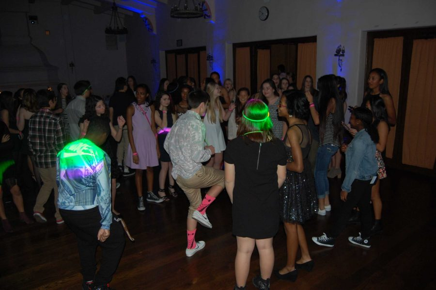 A crowd forms a circle around a boy showing off his skills on the dance floor. Photographer: Kendra Casey '16