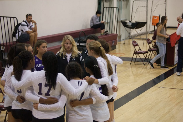 The 2015-2016 Varsity Volleyball team huddles up before starting a pre-season game. The Archer volleyball program consists of three Upper School teams and three Middle School teams.