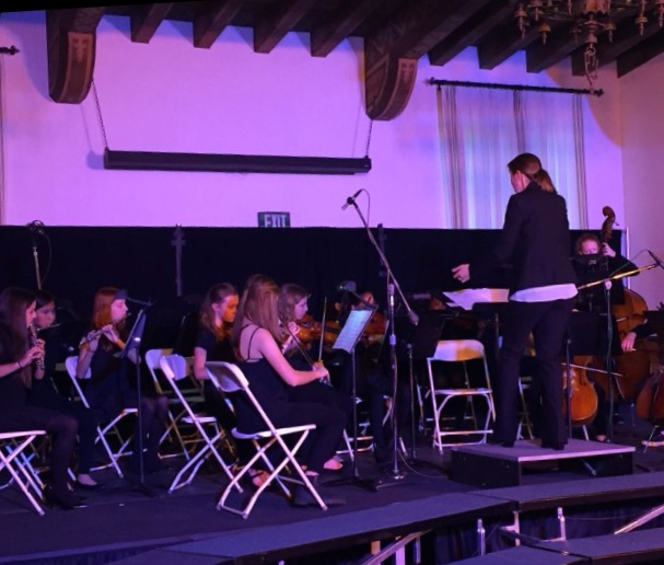 Susan Smith leads the middle school orchestra in song as they preform for the audience. Photographer: Isabelle Wilson'17