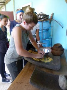 Rachel Lauster was grinding corn to make a tortilla at the Mayan Cultural Center. Used with permission from: Shohfi
