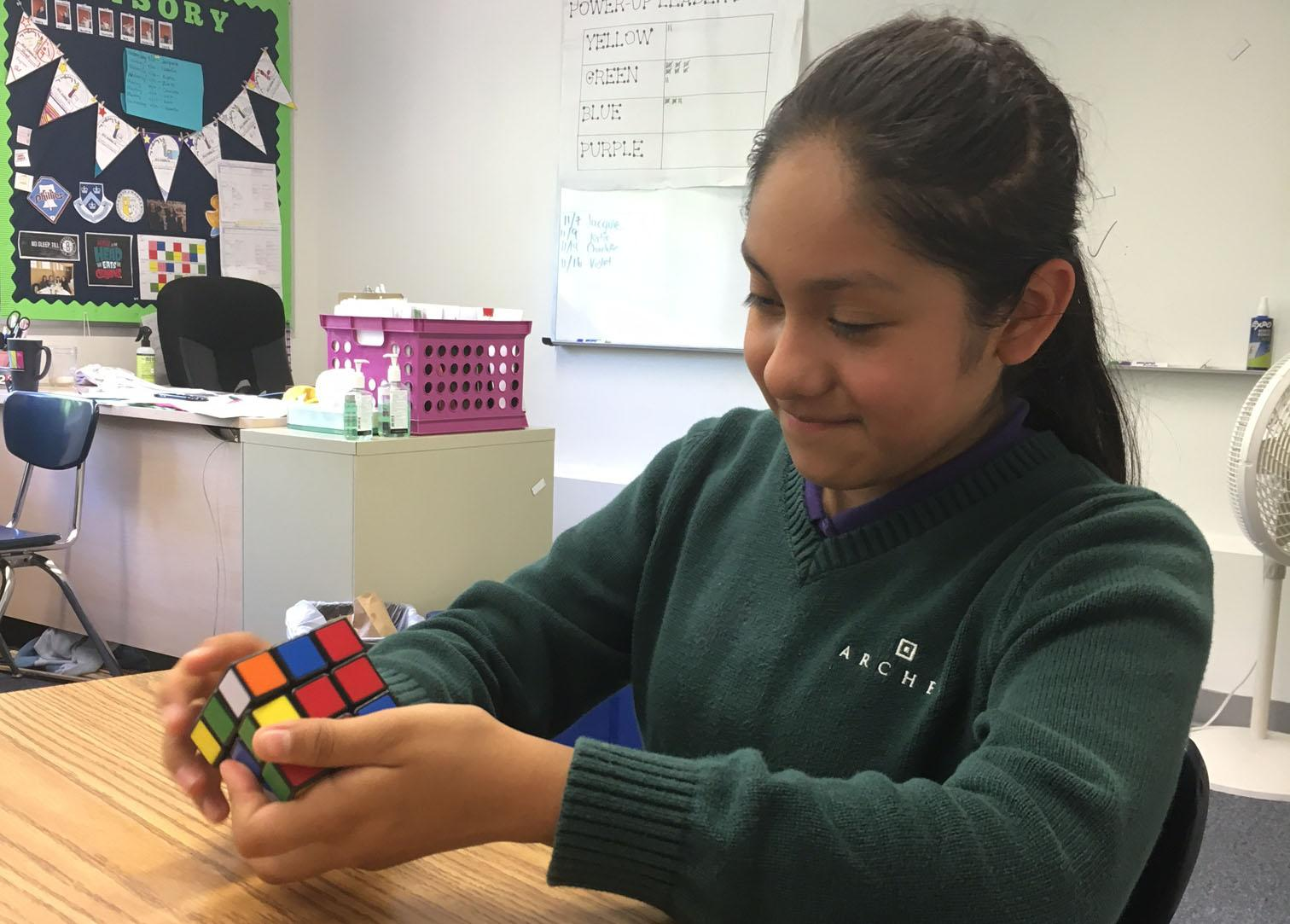 Karen Garcia '23 solves a Rubik's Cube at the team's first meeting. The team completed a simple practice mosaic after brainstorming design ideas.
