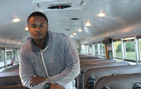 Archer's bus 803 driver An'twon Colvin stands in the bus aisle after a long ride. According to Colvin, bus driving has kept him grounded, and he appreciates Tumbleweed Transportation's support and acceptance.