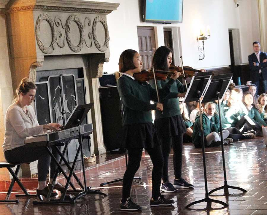 During+a+morning+upper+school+assembly%2C+Audrey+Koh+%2717+and+Sammy+Raucher+%2719+%28from+left+to+right%29+perform+Bach%E2%80%99s+Concerto+for+Two+Violins+in+D+Minor%2C+while+Kate+Burns+plays+piano.+The+goal+of+the+meeting+was+to+celebrate+community+talents.+