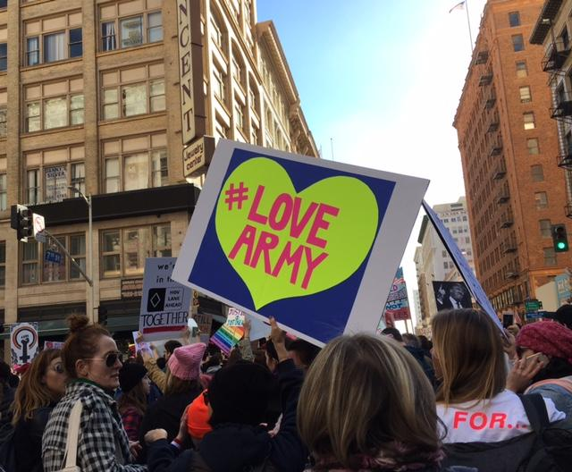 A+protester+bearing+a+sign+reading+%22%23lovearmy%22+marches+towards+the+Los+Angeles+City+Hall+amid+a+sea+of+women%27s+rights+supporters.+Positive+messages+centering+around+love+and+hope+were+commonplace+at+the+Los+Angeles+March.+