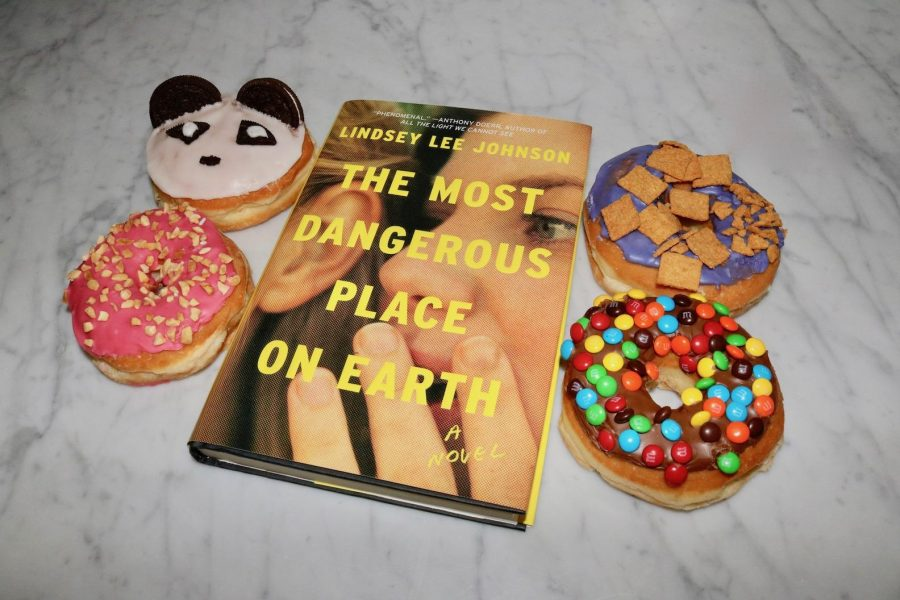 A+copy+of+%22The+Most+Dangerous+Place+on+Earth%22+sits+surrounded+by+doughnuts.+The+book%27s+ominous+title+refers+to+high+school%2C+where+the+story+takes+place.+At+Archer%2C+it+can+often+be+hazardous+when+delicious+food+is+on+campus%2C+particularly+desserts.+We+are%2C+after+all%2C+nicknamed+%22The+Archer+School+for+Food%22+for+a+reason.
