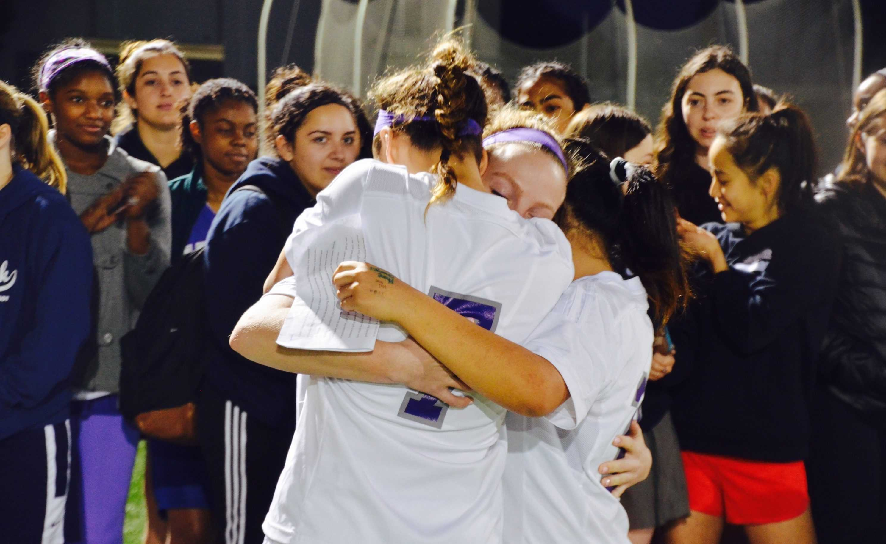 Liadan Solomon '17 (center) hugs Caitlin Mosch '18 (left) and Ruby Colby '19 (right) after hearing their speech for her on Senior Night. The team celebrated their last home game of the regular season with a pre-game ceremony. Image courtesy of Mosch.