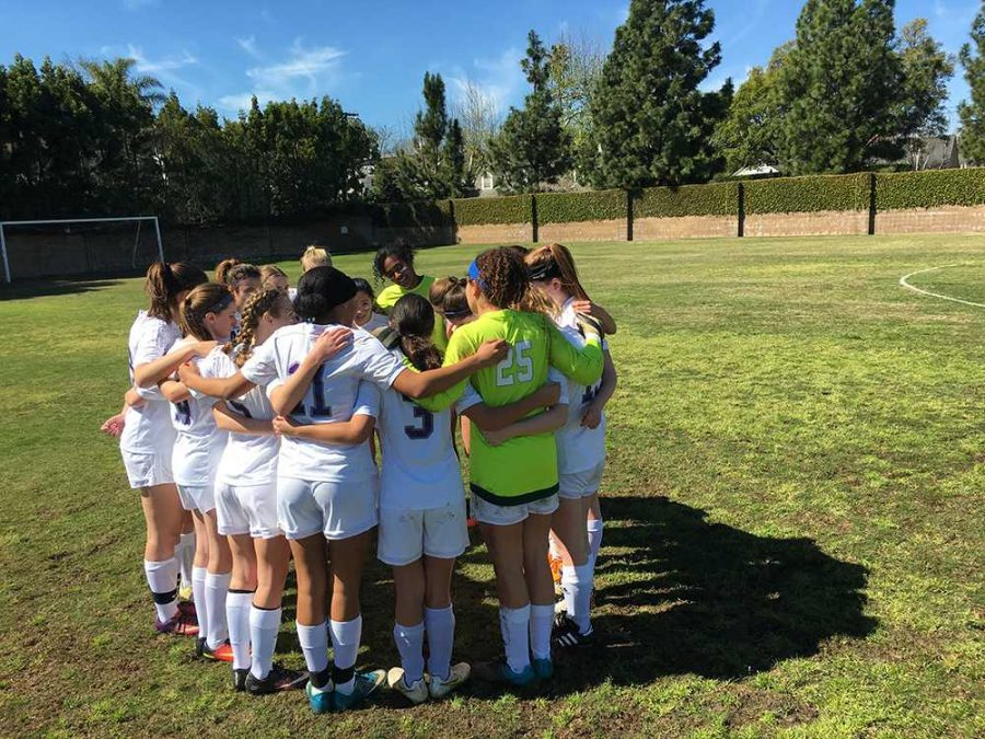 The varsity soccer team huddles before the game. During the huddle, they shared positive words of encouragement.
