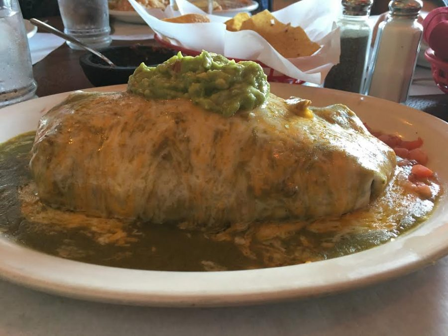 A Super Mex burrito sits on a table. This enormous creation is prepared with fresh tortillas, homemade green sauce, chicken, lettuce, salsa, and cheese.