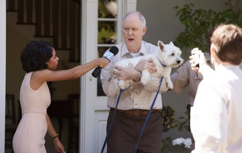 John Lithgow portrays Larry Henderson, a poetry professor accused of murdering his wife. Featured above is an image from the pilot episode, where Larry is being bombarded by news reporters. Image source: NBC's 'Trial & Error' page.