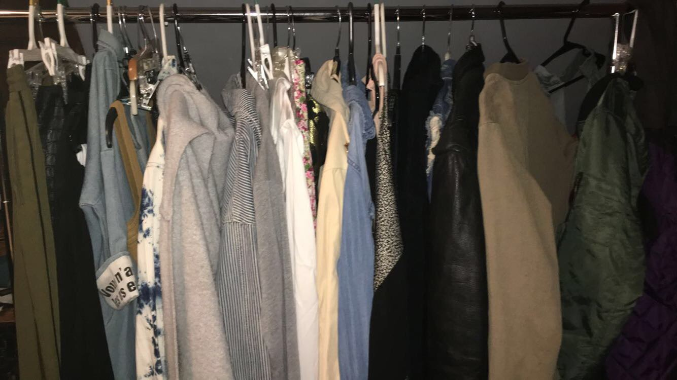 A clothing rack with clothes from several different fast fashion brands. Clothing like this harms the environment and the workers who make it.