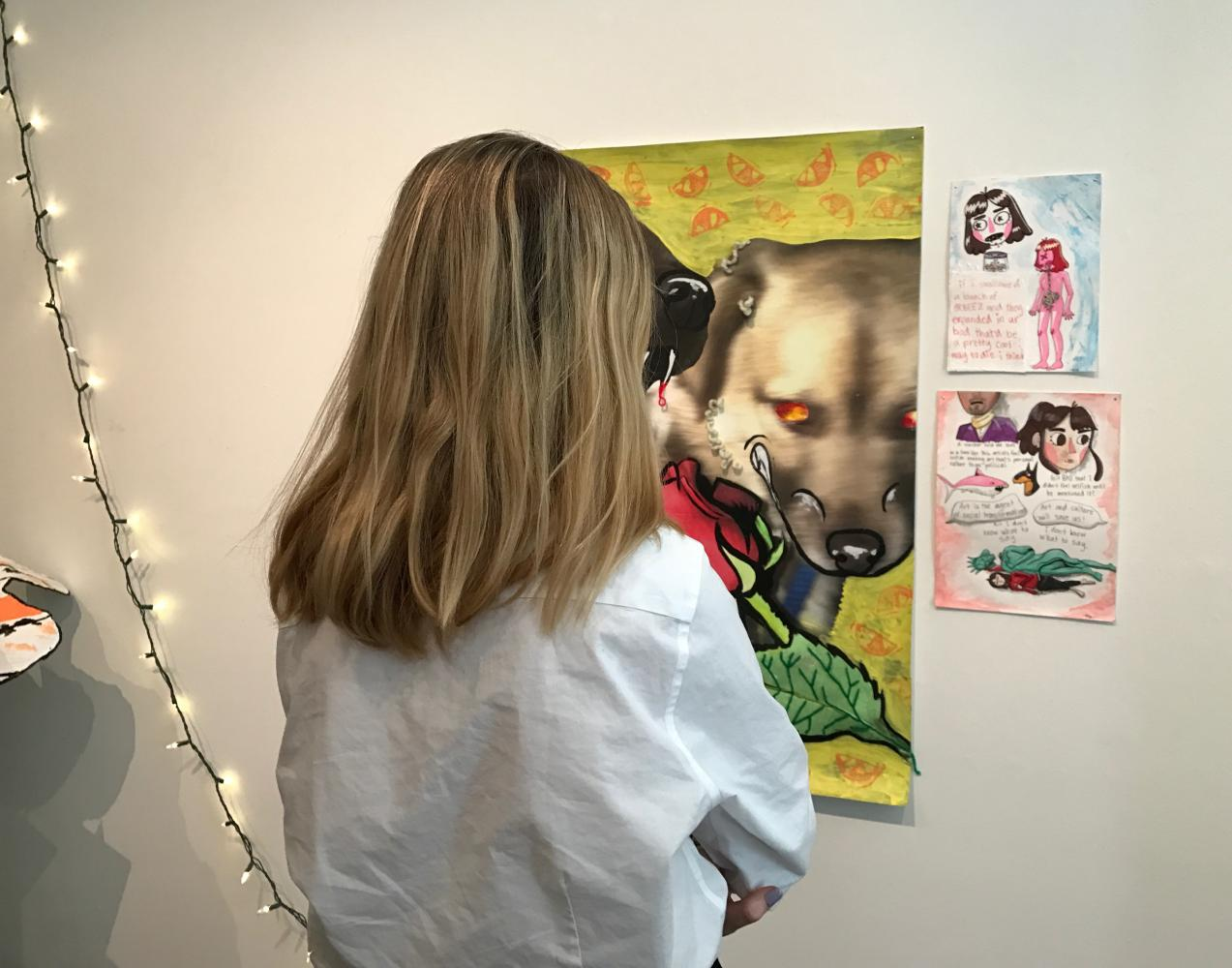 Uma Halsted '18 walks through Elizabeth Zinman's exhibit, entitled
