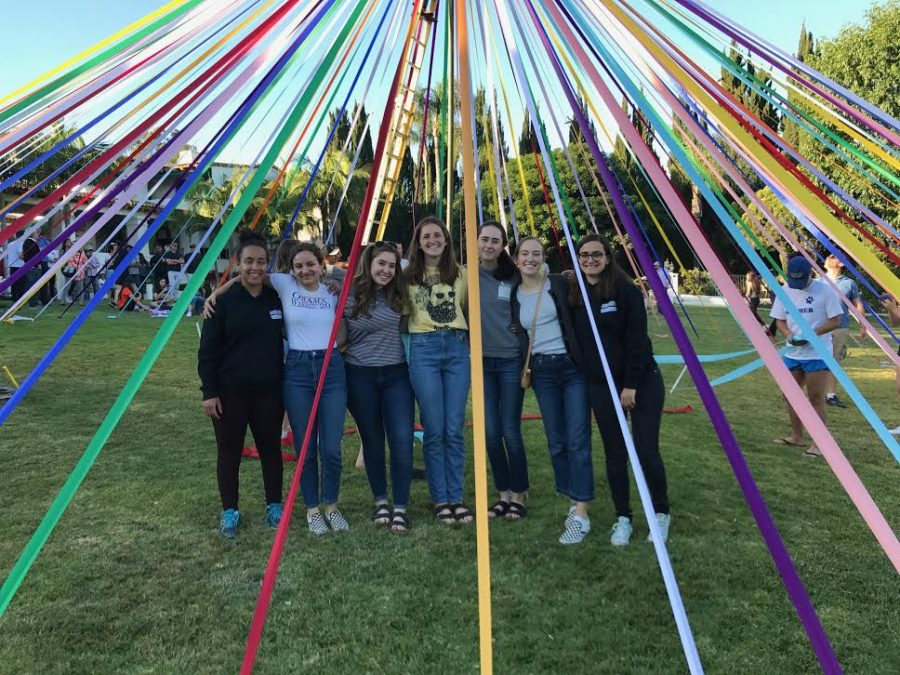Isabel Adler '17 poses with senior friends under the maypole.