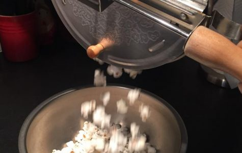 Freshly popped popcorn flows into a metal serving bowl, where it will soon be seasoned and devoured. This is a great snack to enjoy any time of day.