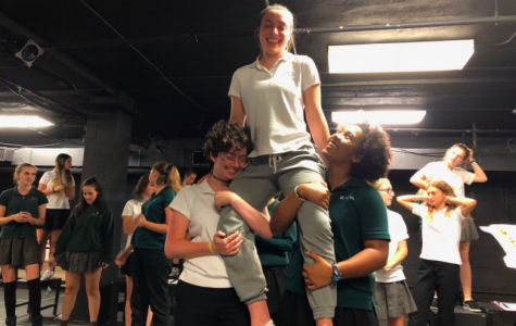 Junior Shira Goldstein, who plays Bat Boy, sits on the shoulders of Willa Frierson '20 and Omari Benjamin '18 during a rehearsal. The original musical was inspired by tabloid headlines published in 1992 in The Weekly World News documenting a half-man and half-bat creature.