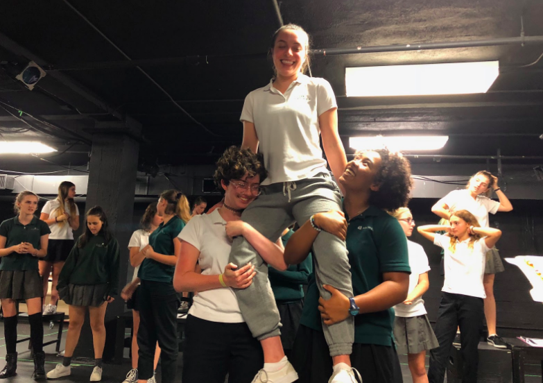 Junior+Shira+Goldstein%2C+who+plays+Bat+Boy%2C+sits+on+the+shoulders+of+Willa+Frierson+%E2%80%9820+and+Omari+Benjamin+%E2%80%9818+during+a+rehearsal.+The+original+musical+was+inspired+by+tabloid+headlines+published+in+1992+in+The+Weekly+World+News+documenting+a+half-man+and+half-bat+creature.+