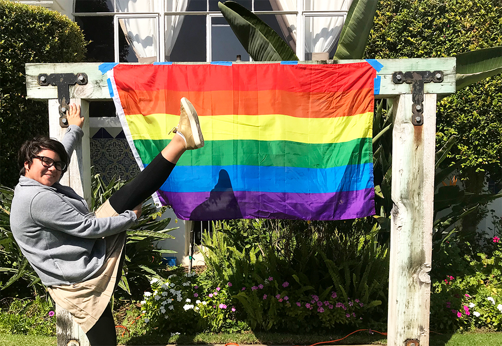 Sophia Caplan '22 kicks her leg in the air in front of the pride flag in the courtyard. This is the first year Archer has celebrated National Coming Out Day in addition to International Day of the Girl.