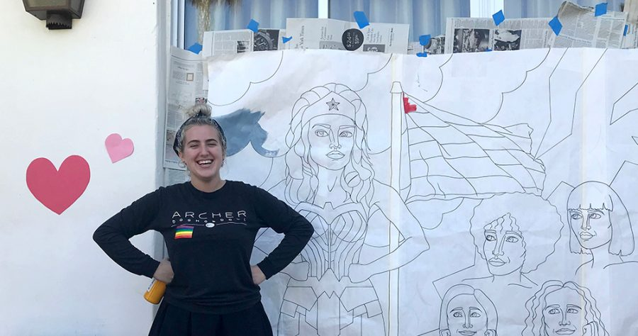 Rose+Shulman-Litwin+%2718+poses+like+Wonder+Woman+in+front+of+the+mural+she+made+for+the+celebration.+Isabel+Kuh+%2719+asked+Shulman-Litwin+to+create+the+mural+as+a+way+to+connect+the+two+celebrations.+