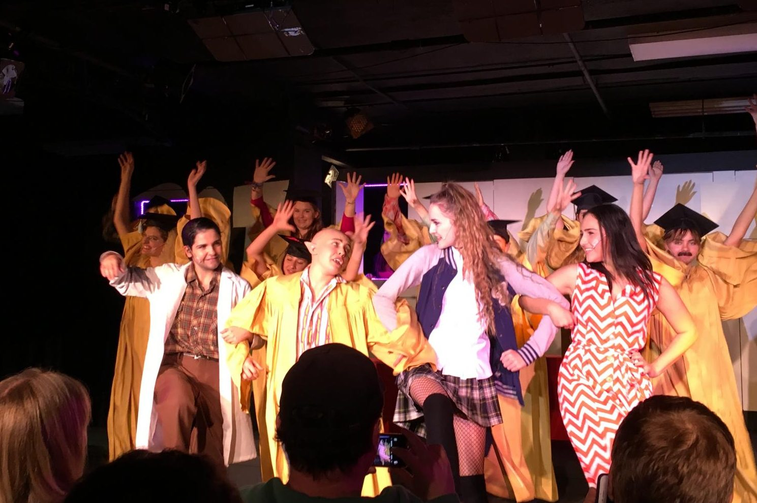 Sophie+Evans-Katz+%2718%2C+Shira+Goldstein+%2719%2C+Dani+Beauregard+%2718+and+Julianna+Goldsmith+%2718+sing+in+front+of+the+entire+cast.+This+scene+depicts+Edgar%27s+high+school+graduation.+