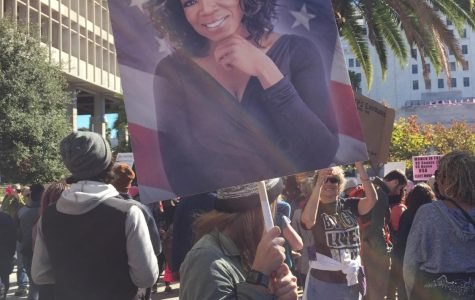 A woman holds a sign of Oprah Winfrey above her head, while listening to a speaker at the 2018 women's march in Los Angeles.  An estimated 500,000 people attended the march in Downtown LA.