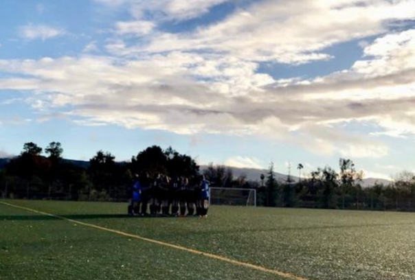 The varsity soccer team huddles before their game against Milken. The team won their first league game of the season with a score of 1-0.