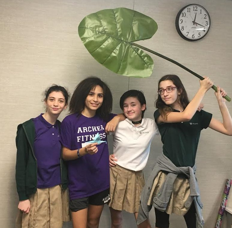 Eighth+graders+and+Leaf+Club+leaders+Zoe+Bush%2C+Glory+Chase%2C+Bess+Frierson+and+Paola+Hoffman+pose+with+their+leaf+mascot+and+a+paper+crane.+The+club+often+does+arts+and+crafts+projects+during+their+meetings.