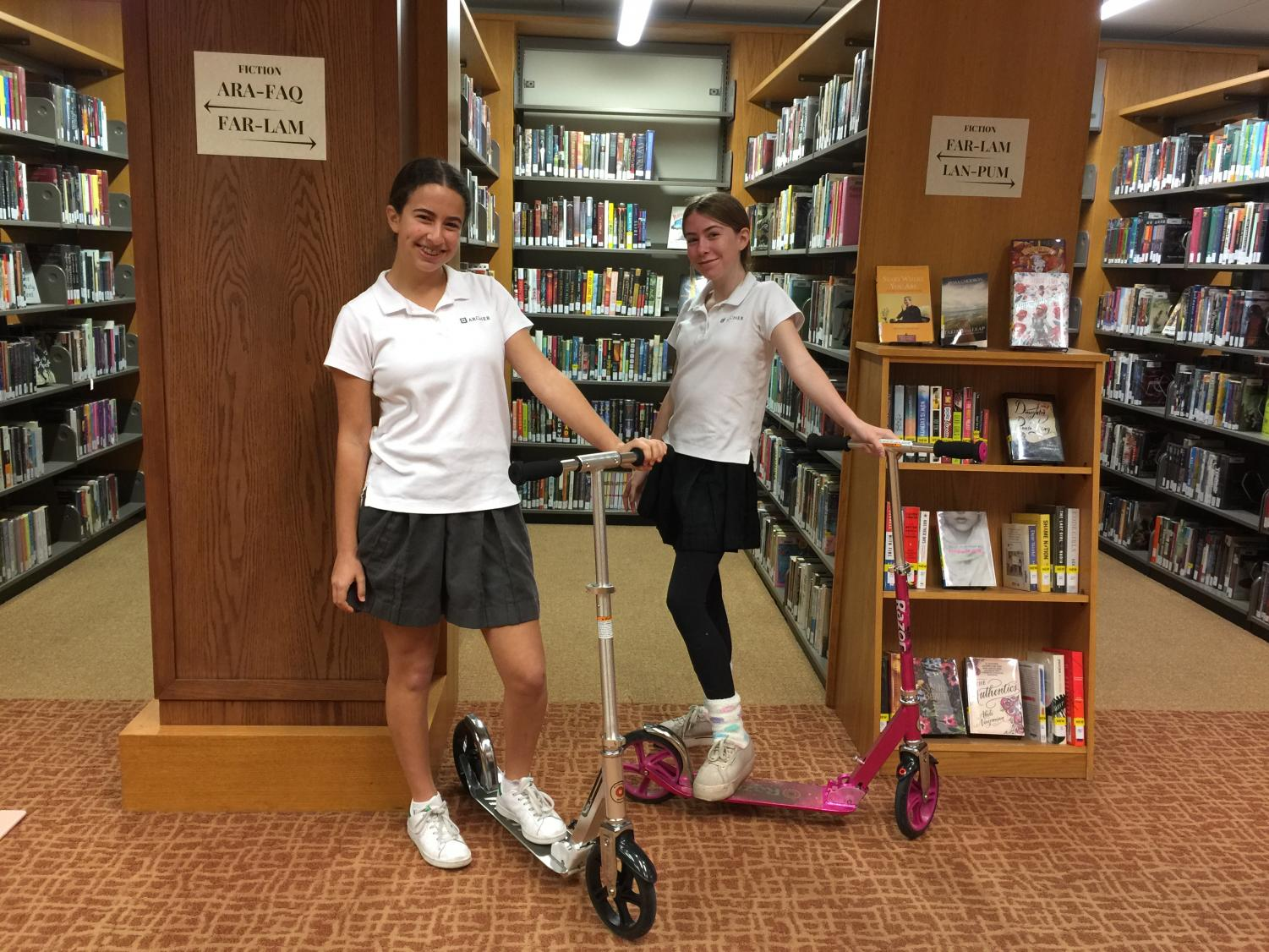 Jessica Tuchin '21 and Shainna Orecklin '21 pose for a picture with their scooters in the library.  Every morning, they drop their scooters off in the library to be stored for the day.