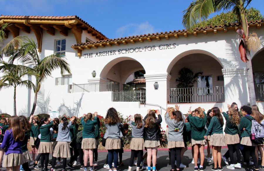 Middle schoolers create a tunnel to welcome the high schoolers back to campus. The younger students were encouraged not to leave the front lawn because of safety precautions.