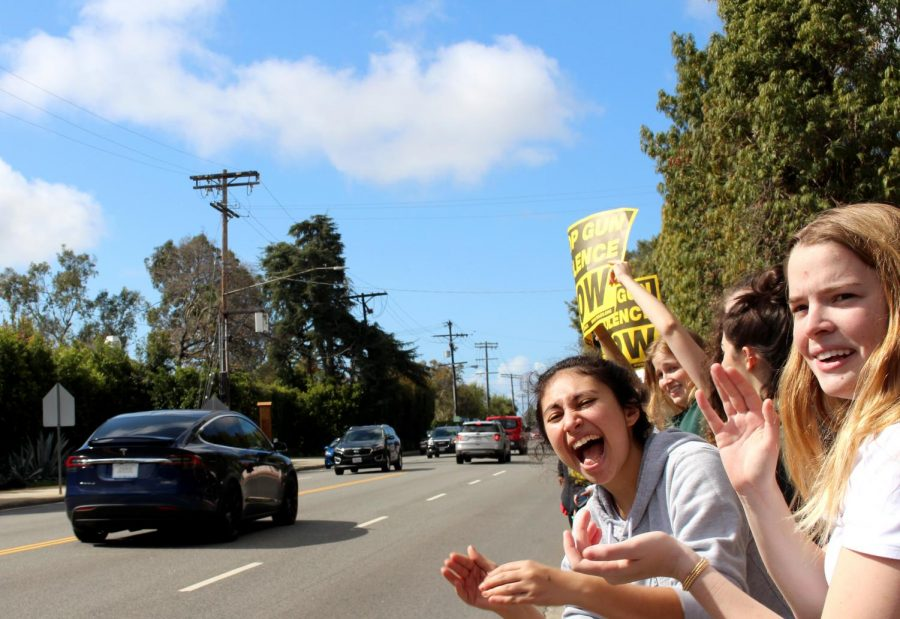 Seniors Jael Ellman and Gracie Marx shout during the protest. Many cars sounded their horns in solidarity.