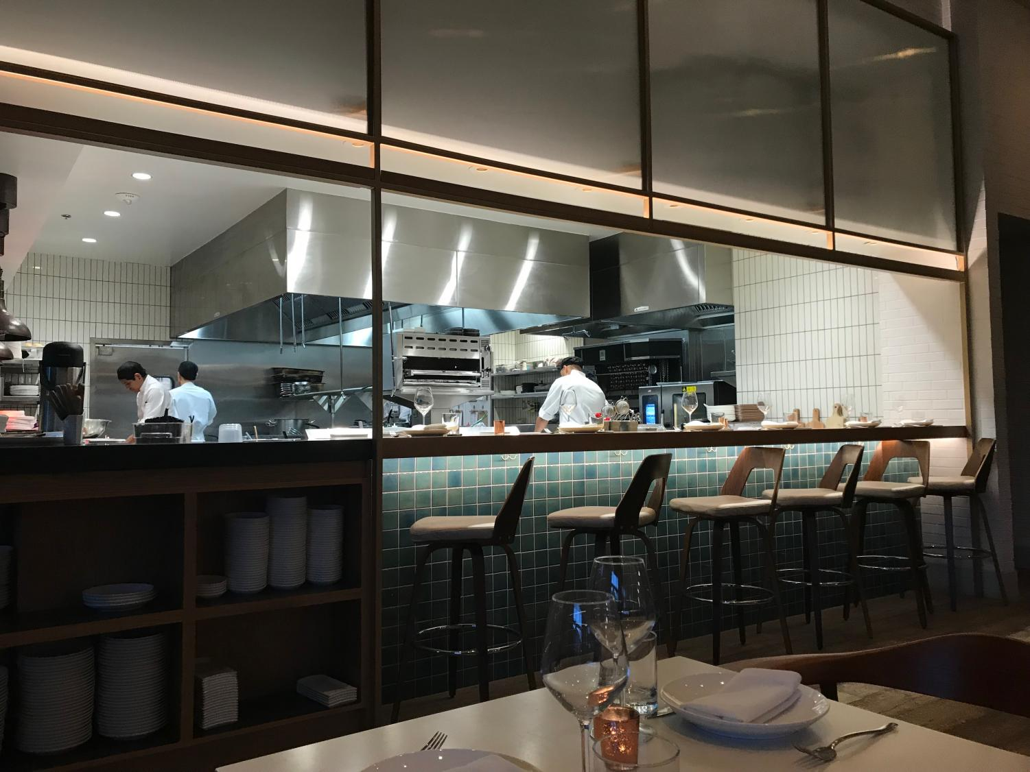 The interior of Dominique Ansel allows customers to have a peek into the kitchen where their food is being prepared. There is both indoor and outdoor seating at this location.