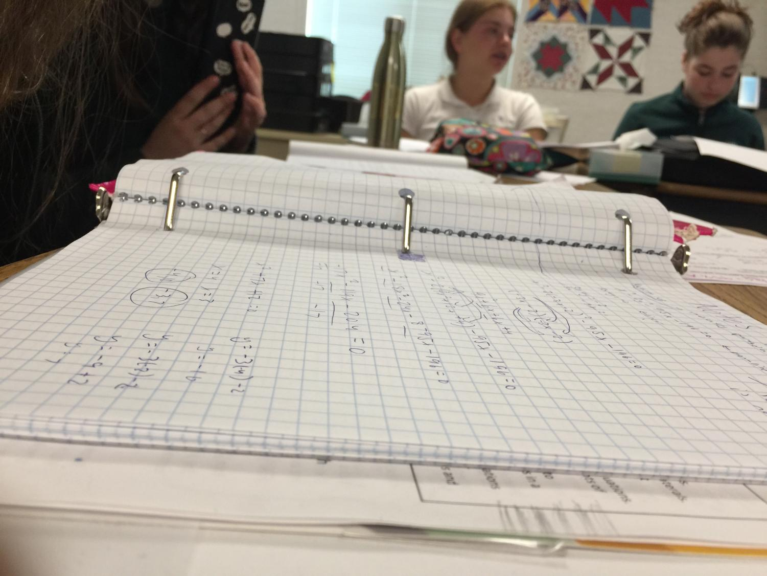 A binder sits on a desk in Leila Chakravarty's math classroom. Her ninth and 10th grade Integrated Math III class completes practice problems on solving quadratic and linear systems of equations.