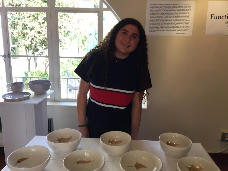 Macoy Ohlbaum '18 poses with some of her ceramic bowls.  She created a series of bowls, cups and other functional objects for the display.