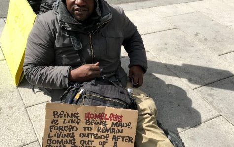 A homeless man poses on the street with a handmade sign. Kornfield takes pictures of homeless people and their signs in order to evoke empathy.