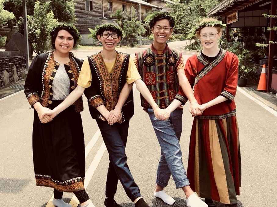 Greene poses in traditional Taiwanese clothing with two classmates and a tutor from Wenzao University. The group visited Tainan, where students learned to make aboriginal Taiwanese foods and perform dances.