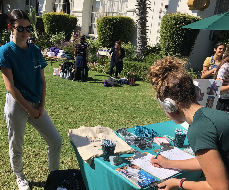 Student signs up at senior Eden Motzkin's booth. Motzkin works with the non-profit Michelson Found Animal Foundation.
