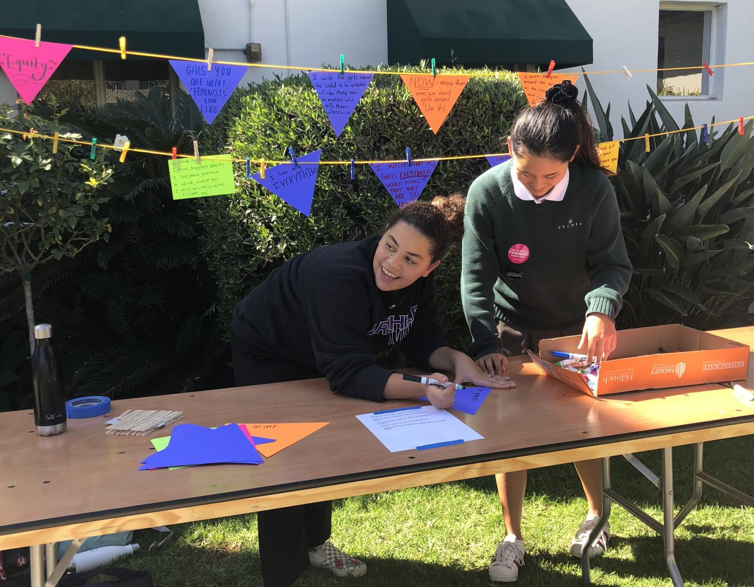 Juliet Youssef '19 and Hannah Kim '20 facilitate pennant-making for International Day of the Girl and National Coming out Day.
