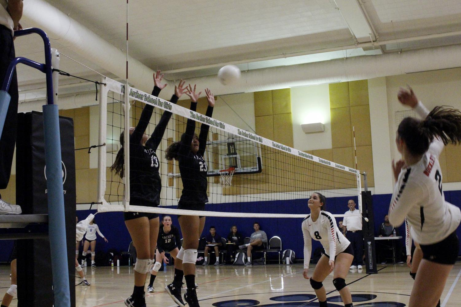 Vaughn Anoa'i '22 and Bella Morgan '21 block the ball as their opponent hits it over the net. The varsity volleyball team will move on to the next round of CIF playoffs next week.