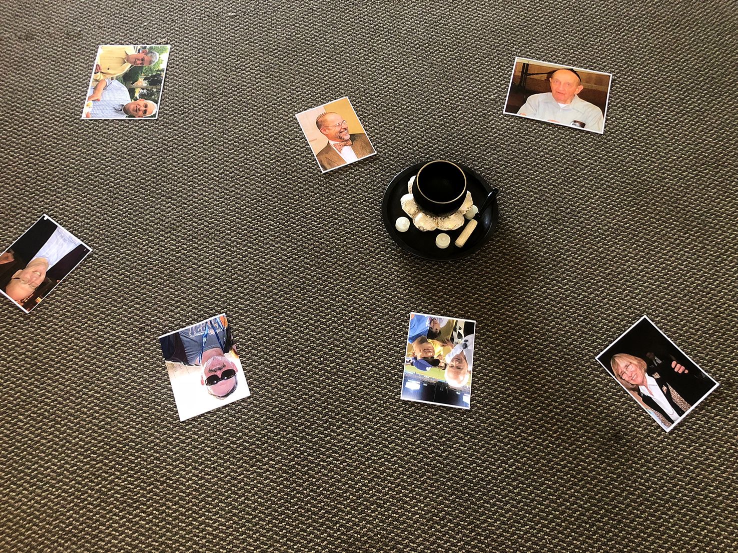 Pictures lie on the ground of the HD room, featuring seven victims of the Tree of Life synagogue shooting in Pittsburgh. JSC placed the pictures around a bowl with candles to honor the victims' memories.