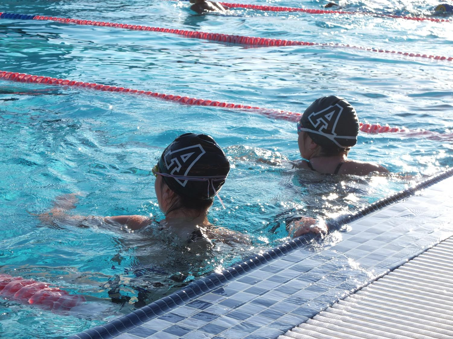 Two swimmers get ready to  push off the wall and begin to swim at the PBL championships. Seventh grader Amelia Hines was named MVP of middle school swim.