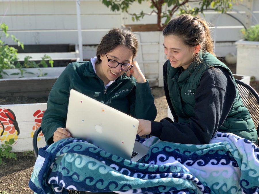 Ella Frey '19 and Allie Worchell '20 sit in the Archer garden while watching