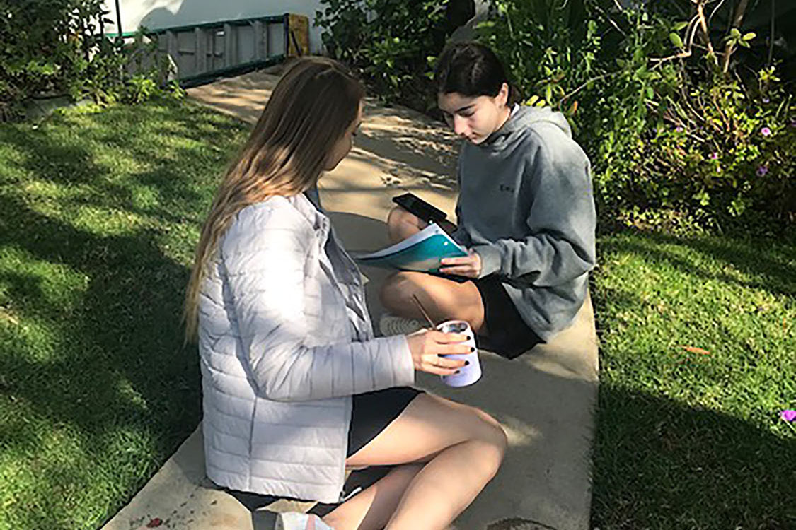 Freshmen London Sinclair and Chloe Fidler sit in the shade in the courtyard during x-block. 'The lavender grey color of the jacket really compliments our uniform colors.' Sinclair said.
