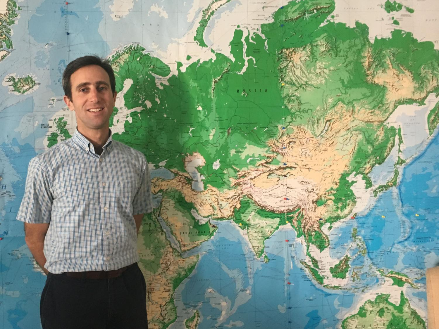 Graham stands in front of a world map in his classroom. Graham previously taught in England.
