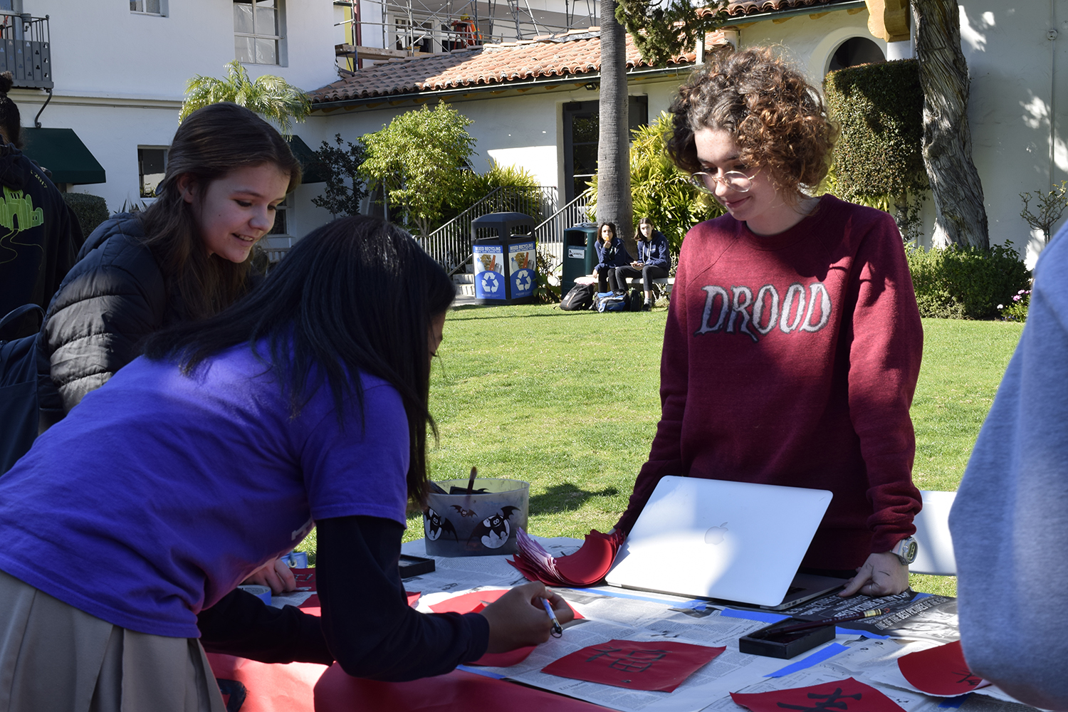 Chinese student Willa Frierson '20 teaches middle schoolers some basic Chinese characters. This booth was one of many at the celebration on Friday, Feb. 8.