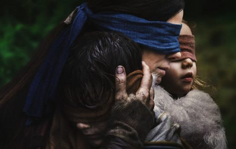 Malorie Hayes, played by Sandra Bullock, holds two children in her arms while wearing a blindfold. Bird Box is set in an apocalyptic world where a monster drives all who see it to kill themselves.