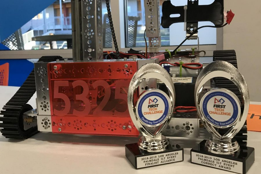 The robotics team robot rests on a table with two awards. The team won the Connect Award and won second place in an alliance during a tournament on February 9.