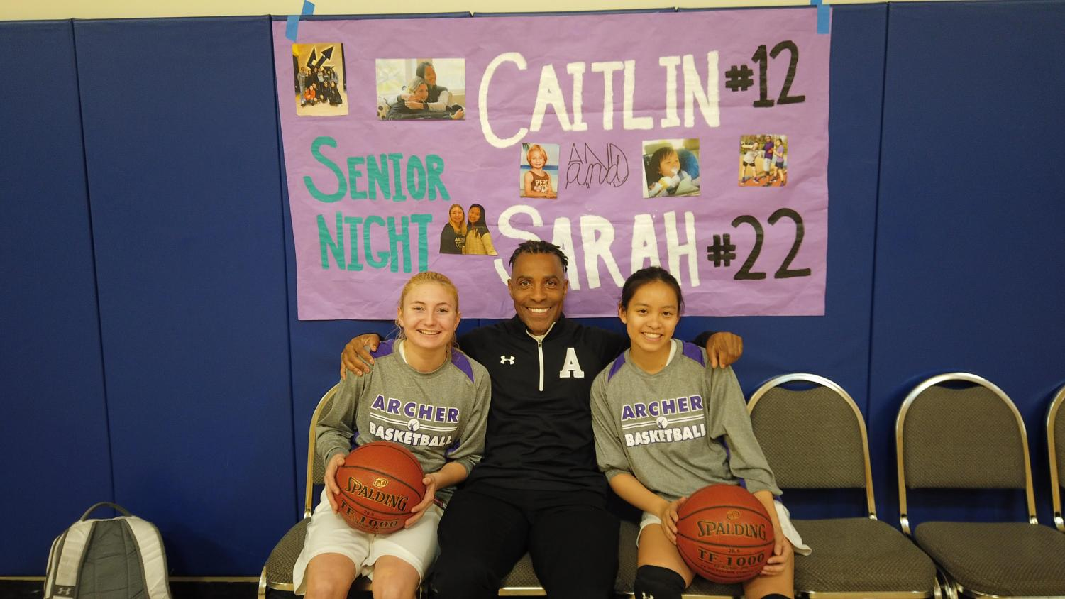 Seniors Sarah Traenkle and Caitlin Chen sit next to their coach, Jelani Bandele. At Thursday's game, the team celebrated Senior Night, which honored Chen and Traenkle.