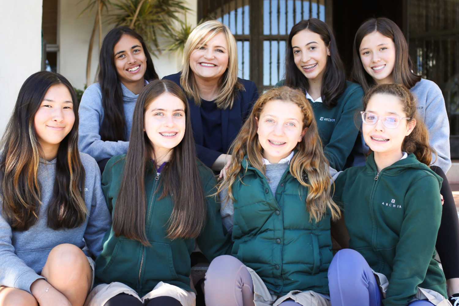 Eighth graders Uma Bajaj, Karen Pavliscak, Daisy Marmur, Genevieve Sieve, Sydney Frank, Juliet Katz, Zoe Woolenberg and Margaret Morris sit with Pavliscak on the front steps. Pavliscak is currently serving as Middle School director and Assistant Head of School and will assume the role of Associate Head at the beginning of July.