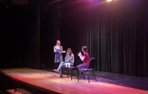 Drama Queens Ava Vinton '20, Livia Blum '19 and Caroline Ediger '19 sit at the Magicoplis theater while performing