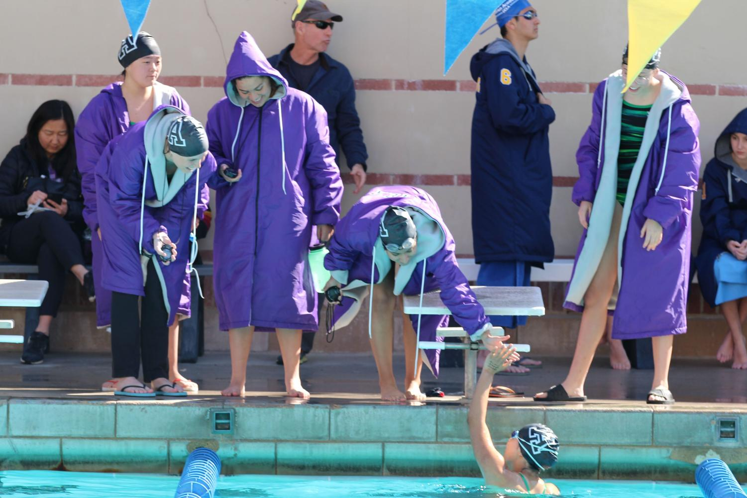 Members of the swim team high-five each other during their last meet before CIF finals. This year, the team qualified for CIF finals in three divisions, the 200 meter individual medley, the 200 meter freestyle and the 100 meter freestyle.