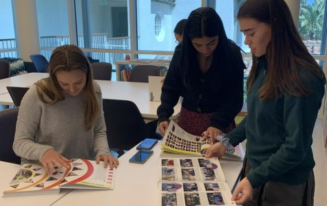 Yearbook copy editor Abigale Lischak '20, photo editor Yasi Gohar '20, and sales manager Julia Wanger '20 flip through the pages of this year's yearbook. The theme of the book is